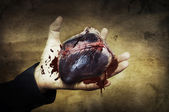 Halloween concept. heart in hand with blood — Stock Photo