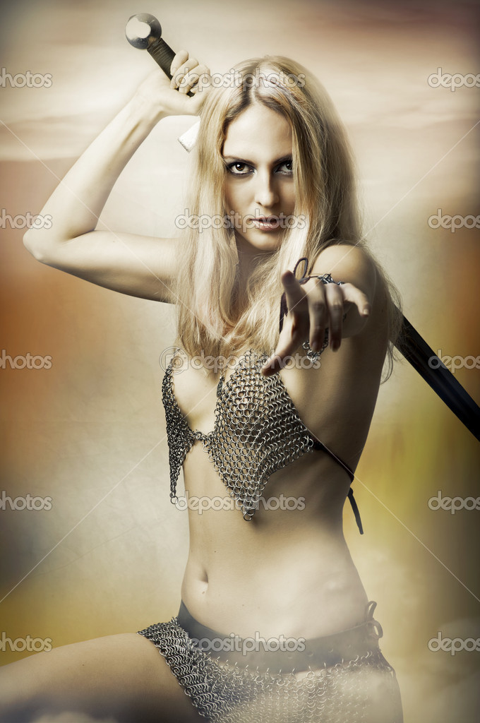 Fantasy portrait of medieval woman fighter with sword in sexy armour pointing at camera. Joan of Arc  Stock Photo #6689564