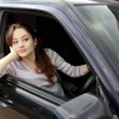 Stock Photo: Beautiful girl is sitting in sport car and looking