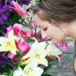 Beautiful girl sniffing bright lilies in the flower garden — Stock fotografie