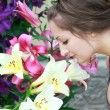 Beautiful girl sniffing bright lilies in the flower garden — Stock Photo #6229212