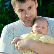 Handsome smiling man holding newborn serious baby girl on the ha — Stock Photo
