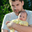 Thoughtful man holding serious little baby on the hands in park — Stock Photo