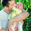 Handsome young father kissing his little baby on green tree back — Stock Photo