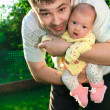 Stock Photo: Father holding newborn joyful baby girl on hands on nature g