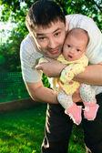 отец холдинг новорожденных радостное девочку на руки на природе g — Стоковое фото