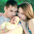 Happy family. Mother and father kissing their daughter with love — Stockfoto