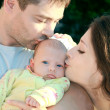 Parents kissing beautiful blue eye baby girl on nature. — Stock Photo