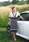 Beautiful young woman standing near white sport car — Stock Photo