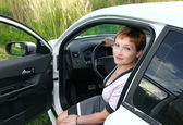 Beautiful smiling woman sitting behind the wheel of sport car wi — Stok fotoğraf