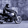 Man riding a motorcycle on the road - Stock Photo