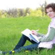 Girl student in park writes in writing book - Stock Photo