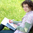 Girl student in park writes in writing book — Stock Photo