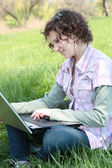 Girl with a laptop on the spring meadow — Stock Photo