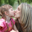 Little girl kissing her mother in a park — Stock Photo