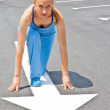 Athletic woman in start position on track — Stock Photo