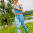 Stock Photo: Young woman jogging in the park in summer