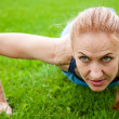 Caucasian female doing push ups in the park - Stock Photo
