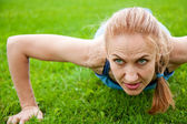 Caucasian female doing push ups in the park — Stock Photo