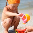 Cute girl playing with beach toys on tropical beach — Stock Photo #6299397