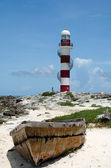 Old boat decaying in front of Punta Cancun lighthouse and a girl in white d — Stock Photo