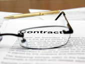 Glasses and pen on the contract papers — Stock Photo