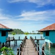 Wooden footbridge into the water bungalows - Stock Photo