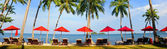 Panorama of perfect tropical beach with red umbrellas — Stock Photo