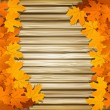 Vector autumn leaves on the background of a wooden wall — Stock Vector #6009552