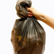Woman holding a full black plastic trash bag in his hand. — Stock Photo #5871075
