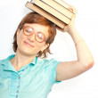 Girl in glasses with books on head — Stock Photo