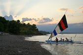 Small sailing boat and sunset sky - landscape scene in Bali. — Stock Photo