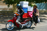 Motobike driver with a passenger carries boxes in Phnom Penh, Cambodia. — Stock Photo