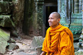 A monk sits on ruins of the Wat Ta Phrom temple at Angkor Wat in Cambodia — Fotografia Stock