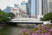Anderson bridge in Singapore with The Fullerton Hotel on background. — Stock Photo
