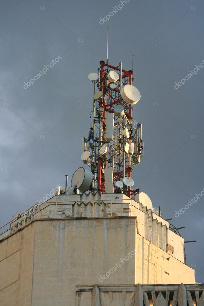Modern communication antenna on a building over cloudy sky — Stock Photo #6207487