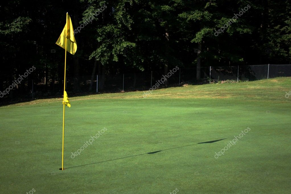 Golf flag on the green casting a shadow — Stock Photo #6404202