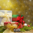Stock Photo: Three presents decorated with gold satin and Christmas decoratio