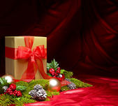 Present decorated with red satin and Christmas decoration — Stock Photo
