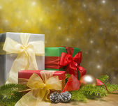 Three presents decorated with gold satin and Christmas decoratio — Stock Photo