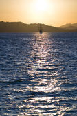 Sailboat bathed in dawn sunlight — Stock Photo