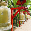 Row of bells in a temple covered by red umbrella - Stock Photo