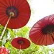 Stock Photo: Three red umbrellin outdoor setting