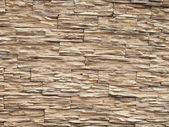 A wall covered with light stone ribbed texture. — Stock Photo