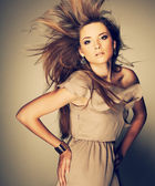 A beautiful young woman is in brown clothes — Stock Photo
