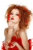 Beautiful redheaded girl with red feathers — Stock Photo