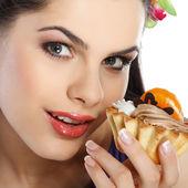 Jeune, belle brune avec gâteau de fruit isolé sur blanc — Photo