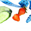 Two pieces of cucumber, strawberries and a metre measure ruler — Stockfoto