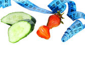 Two pieces of cucumber, strawberries and a metre measure ruler — Stock Photo
