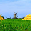 A windmill and haystacks at the beautiful countryside — Stockfoto
